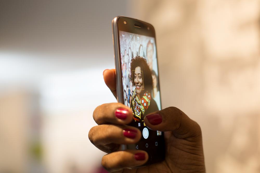 Descrição da Imagem: Eliana Filinto tirando uma selfie com o seu smartphone da Motorola, o modelo moto z2 play.