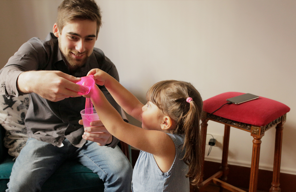 Pedro e Valentina brincando com slime antes de sair de casa, enquanto o moto g⁷ carrega no Turbo PowerTM