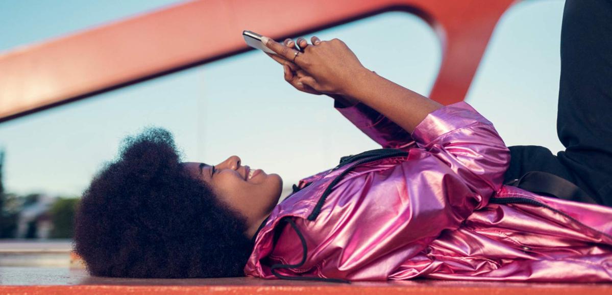 mulher com uma blusa rosa, deitada em um chão liso amarelo, checa seu celular, em frente a um pilar vermelho