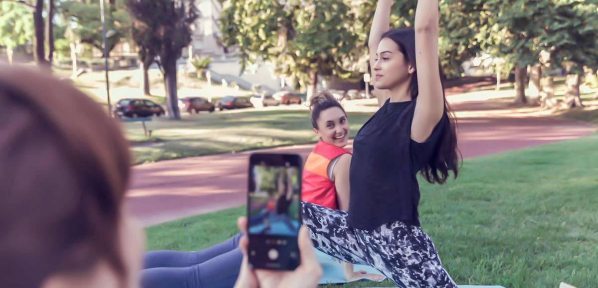 mulheres sentadas em um parque fazem poses de yoga e posam para a câmera de um celular