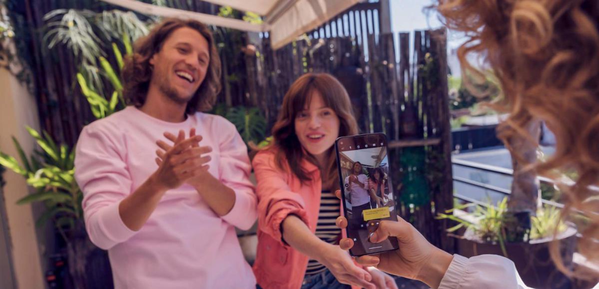homem e mulher sentados em um bar com plantas no fundo, sorriem para a camera de um celular